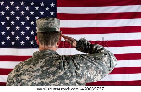 Male Veteran soldier, back to camera, saluting United States of America flag.