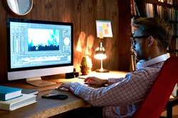 Male videographer editor film maker using pc computer editing video footage visual content working on pc at home office using post production video editing multimedia montage digital software concept.