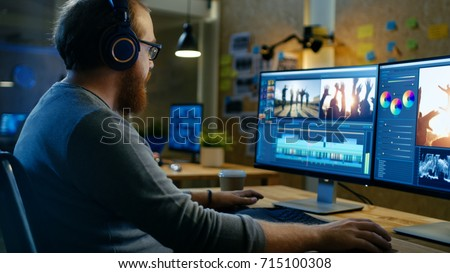 Male Videographer Edits and Cuts Footage and Sound on His Personal Computer, Puts on His Monitors/ Headphones. His Office is Modern and Creative Loft Studio.