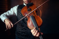 Male violinist playing classical music on violin