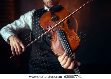 Male violinist playing classical music on violin #630887741