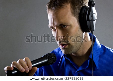 male voice over artist or singer on a microphone wearing a blue shirt on a concrete background
