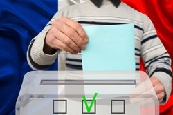 male voter drops a ballot in a transparent ballot box against the background of the national flag of France, concept of state elections, referendum