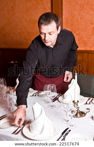 Male waiter arranges dishes on the table in a restaurant