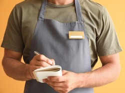 Male waiter with blank badge on color background