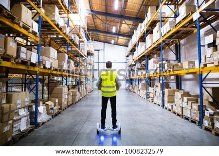 Male warehouse worker on hoverboard. #1008232579