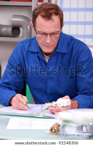 Male warehouse worker with replacement part - stock photo