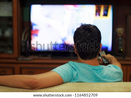 Male watching television in home living room / channel hopping #1164852709