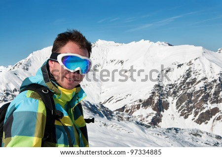 Male wearing goggles and ski jacket smiling on top of high european alps mountains