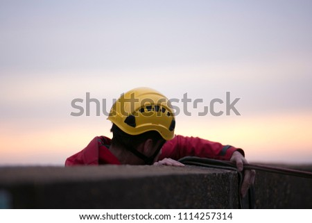 Male wearing industrial yellow rope access safety full protection helmet before climbing over the edge in the morning winter month on construction building site Sydney city CBD, Australia