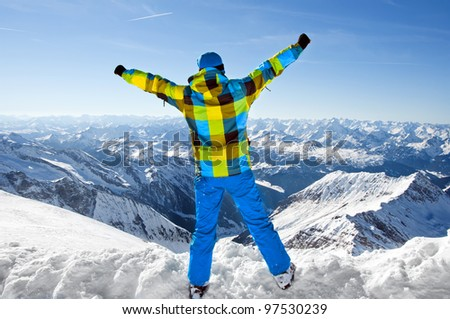 Male wearing ski equipment being excited about climbing on top of European Alps on a sunny winter day