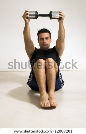 Male weightlifter / athlete doing a sit-up with a dumbbell weight.
