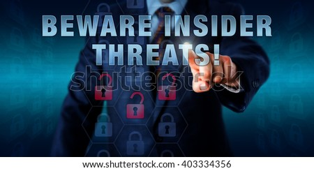 Male white collar worker is pressing BEWARE INSIDER THREATS! on a touch screen. Business challenge metaphor, information technology and computer security concept for insider-caused loss of data. #403334356