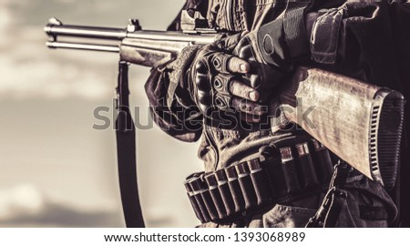 Male with a gun. A hunter with a hunting gun and hunting form to hunt. Hunter man. The man is on the hunt. Hunter with a backpack and a hunting gun. Black and white.