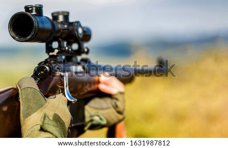 Male with a gun. Close up. Hunter with hunting gun and hunting form to hunt. Hunter is aiming. Shooter sighting in the target. The man is on the hunt. Hunt hunting rifle. Hunter man. Hunting period.
