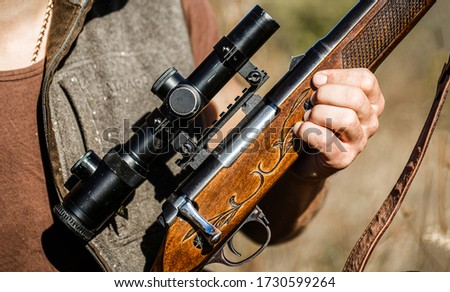Male with a gun, rifle. Process of hunting during hunting season. Male hunter in ready to hunt. Closeup. The man is on the hunt, sport. Hunter man. Hunting period. Man is charging a hunting rifle.