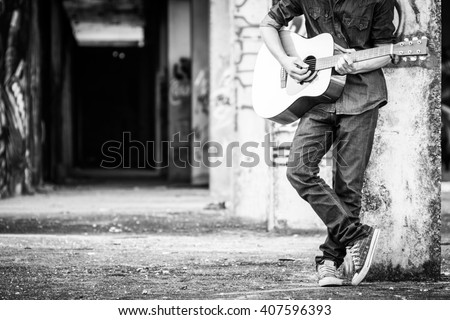 Male with acoustic guitar outdoor, Black and white photo #407596393