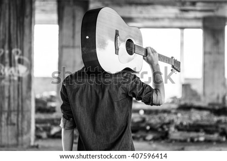 Male with acoustic guitar outdoor, Black and white photo #407596414
