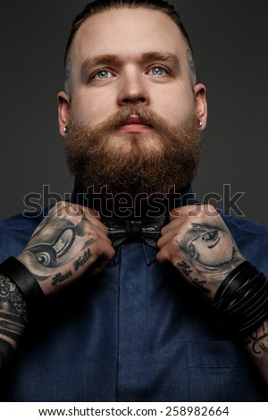 Male with beard and tatoos in blue shirt and bow tie. Isolated on dark grey background.