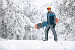 Male with snowboard at winter holiday in mountain