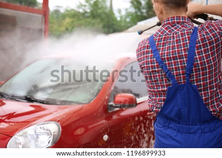 Male worker cleaning vehicle with high pressure water jet at car wash #1196899933