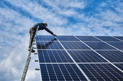 Male worker electrician repairing photovoltaic solar module, standing on ladder under beautiful cloudy sky, installing solar photovoltaic panel. Concept of alternative energy sources and innovations.