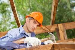 Male worker hammering nail on wooden cabin at construction site