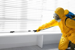Male worker in protective suit spraying insecticide on window sill indoors. Pest control