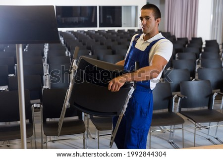 Male worker in uniform carrying chairs in empty conference room