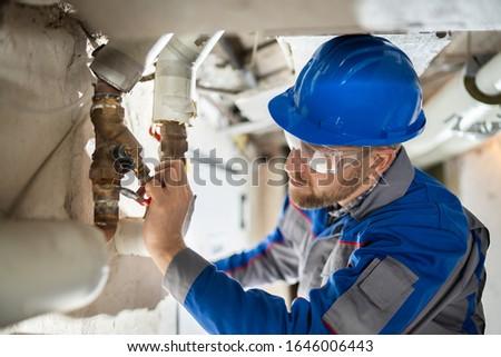Male Worker Inspecting Water Valve For Leaks In Basement
