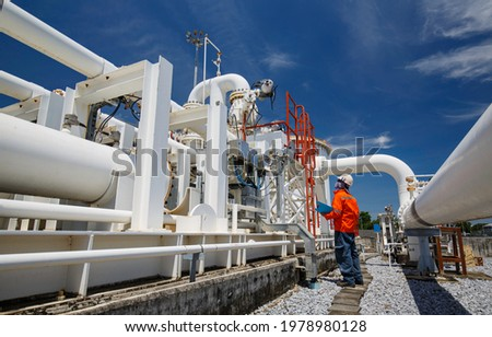 Male worker inspection at steel long pipes and pipe elbow in station oil factory during refinery valve of visual check record pipeline oil and gas industry