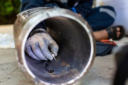 Male worker inspection ultrasonic thickness pipe steel material caused by rust Old rusted iron background concepts, Male hand close-up copying area