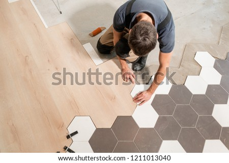 Male worker installing new wooden laminate flooring. The combination of wood panels of laminate and ceramic tiles in the form of honeycomb. Kitchen renovation. Foto stock ©