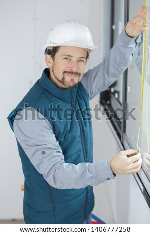 male worker installing window shades at site #1406777258