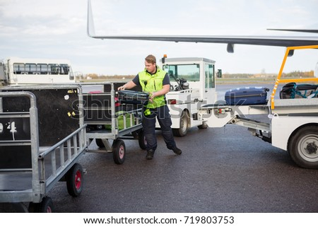 Male Worker Placing Luggage In Trailer On Runway #719803753