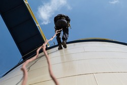 Male worker rope access  inspection photo from the bottom of the fuel tank's.