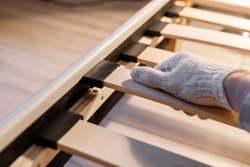 Male worker's hand in glove assembling bed, connecting slats to bed frame
