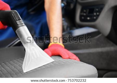 Male worker using vacuum cleaner in car #753702232