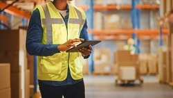 Male Worker Wearing Hard Hat Checks Products Stock and Inventory with Digital Tablet Standing in Retail Warehouse full of Shelves with Goods. Distribution, Logistics. Close-up Shot.