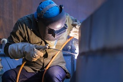 Male  worker wearing protective clothing and repair welding plate industrial construction oil and gas or  storage tank inside confined spaces.