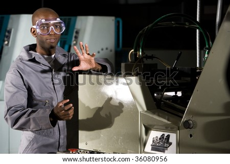 Male worker wearing protective gear beside a printing press
