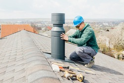 male worker with blue helmet installs an iron chimney. worker with sunglasses repairing chimney on roof.