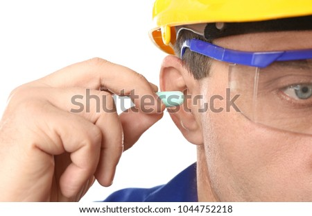 Male worker with ear plug, closeup. Health and safety at workplace concept