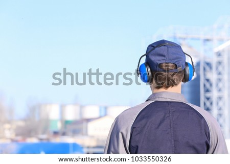 Male worker with headphones outdoors. Hearing protection equipment #1033550326
