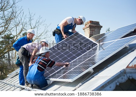 Male workers installing solar photovoltaic panel system. Group of electricians mounting blue solar module on roof of modern house. Alternative energy ecological concept.