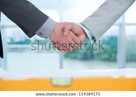 Male workers shaking hands over industrial blueprints and level