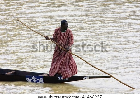 MALI - AUGUST 16: African man pinnace navigating the river Niger in Mopti, most important commercial port of Mali, August 16, 2009 in Mopti, Mali