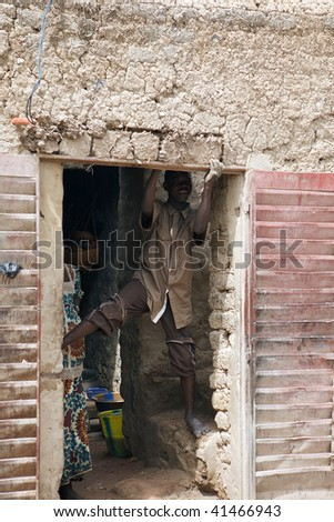 MALI - AUGUST 16: Young African repairing home after the rainy season in Mopti, August 16, 2009 in Mopti, Mali