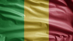Malian flag waving in the wind. Close up of Mali banner blowing, soft and smooth silk. Cloth fabric texture ensign background.