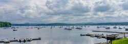 Mallets Bay on Lake Champlain, with many sailboats moored with the Green Mountains of Vermont across the lake